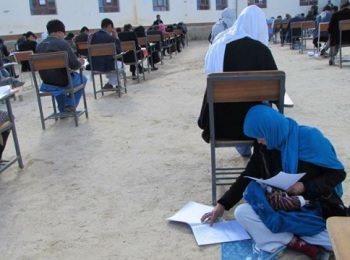 Jahantab Ahmadi nursing her infant daughter while taking a university entrance exam