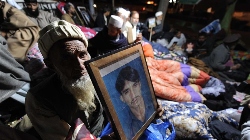 A Pakistani old man holds a picture of his relative during a sit-in protest in a camp set up by families of missing people at D Square outside the parliament on December 12, 2013 in Islamabad, Pakistan.
